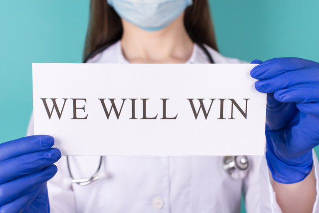 Nurse with 'We Will Win' sign
